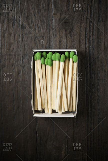 Overhead view of green matchsticks in box on wooden table