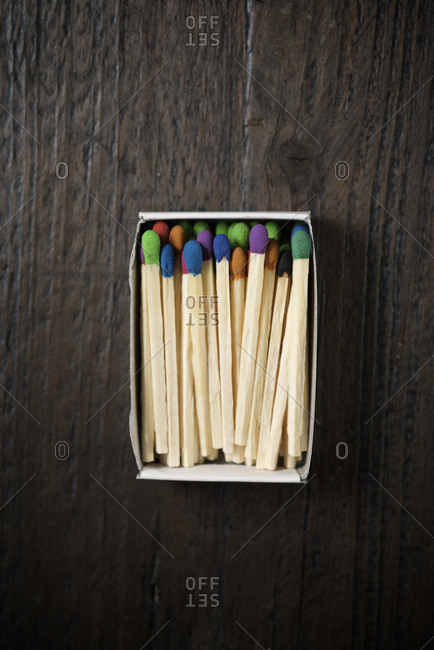 Overhead view of colorful matchsticks in box on wooden table