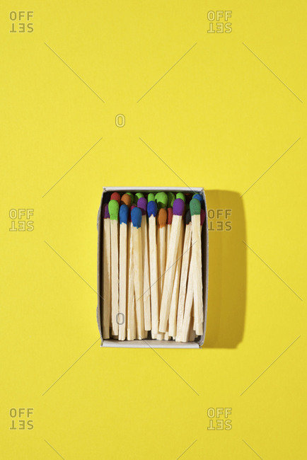 Overhead view of colorful matchsticks in box on yellow background