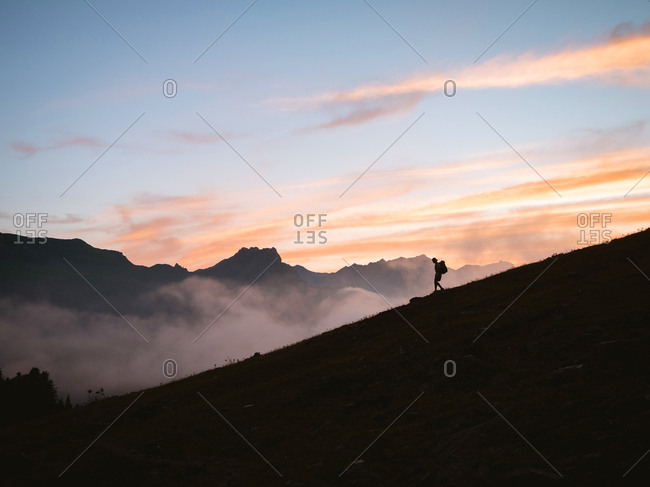 Silhouette of hiker walking down a mountain at sunset
