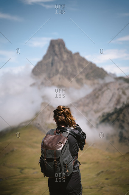 Young blonde woman taking photographs of the landscape in French Pyrenees during a hike