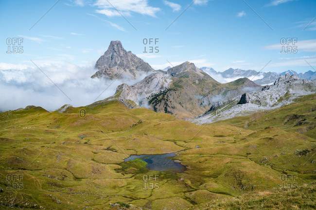 Natural alpine lake in Pyrenees with epic mountains in the background