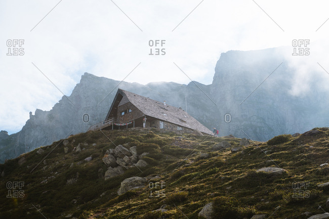 Hiker approaches a mountain hut on a misty day