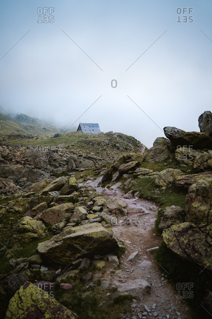 Trail leading to a mountain hut on a foggy day