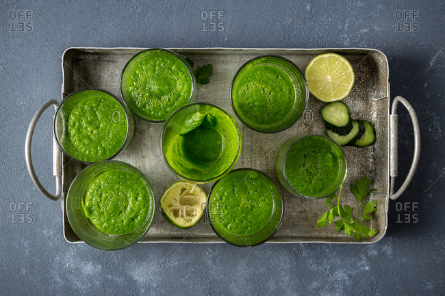 Overhead view set of green smoothies on a dark background