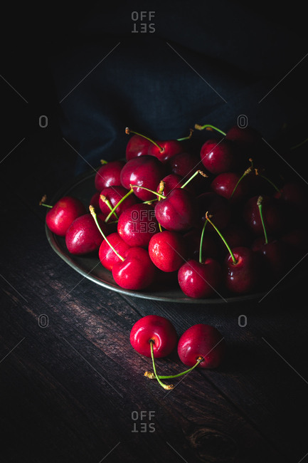 Dark red cherries on a pewter plate. Low light, upright composition.