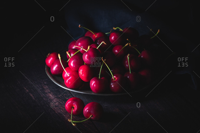 Dark red cherries on a pewter plate. Low light, horizontal composition.