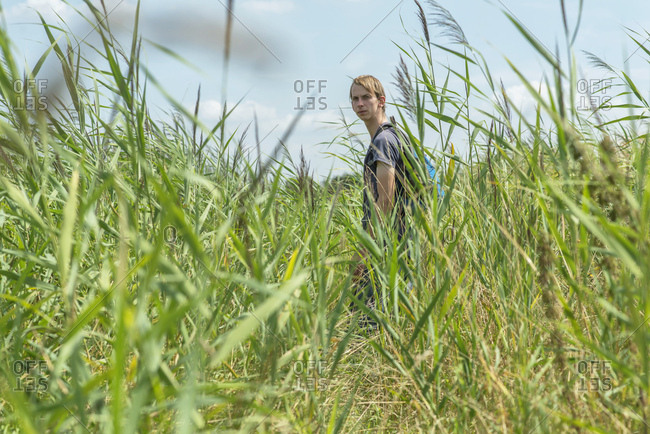 Young man with backpack walking in a field
