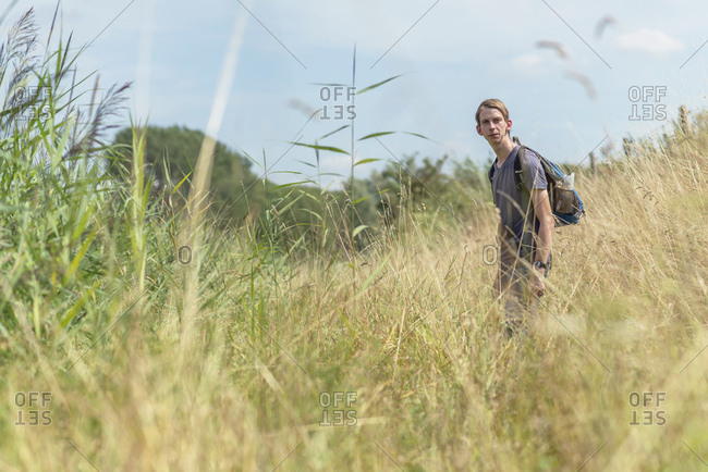 Young man with backpack walking in a rural field
