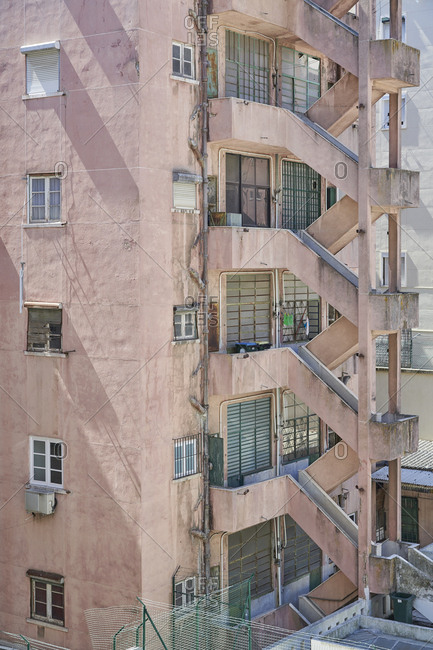 Old pink apartment building with fire escape in the city of Lisbon, Portugal