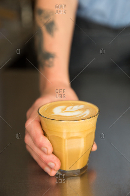 Barista serving a cappuccino in a cafe