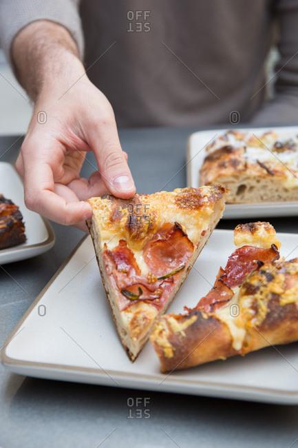 Hand grabbing a slice of flatbread pizza