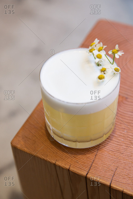 Close up of a foamy cocktail garnished with flowers