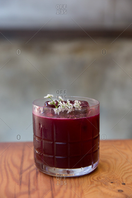 Close up of a beet cocktail garnished with flowers