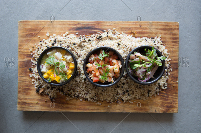 Variety of ceviche dishes in bowls over a bed of rice