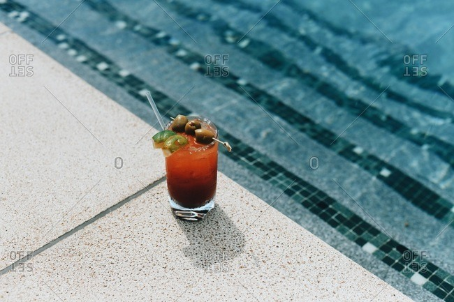 Red drink with olives and lime poolside