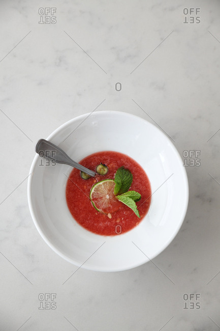 Overhead view of a red fruity dish with lime and mint