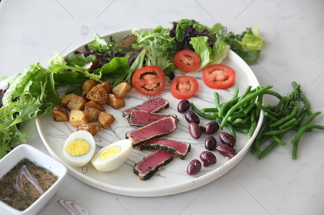 Ahi tuna appetizer served with salad, olives, eggs, tomato and green beans