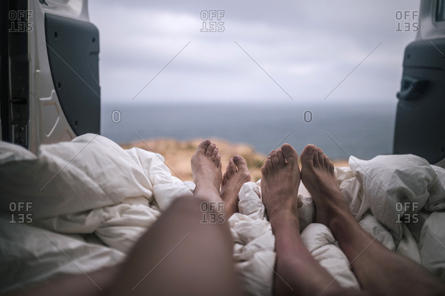 Legs of a couple lying in a van in front of the sea
