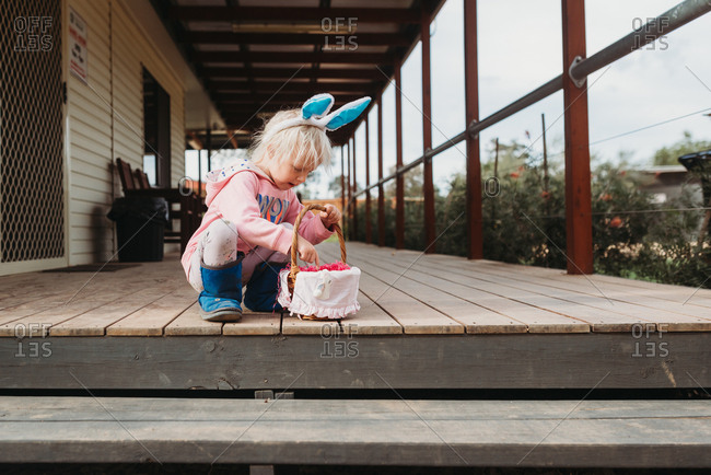 Young child collecting Easter eggs wearing bunny ears