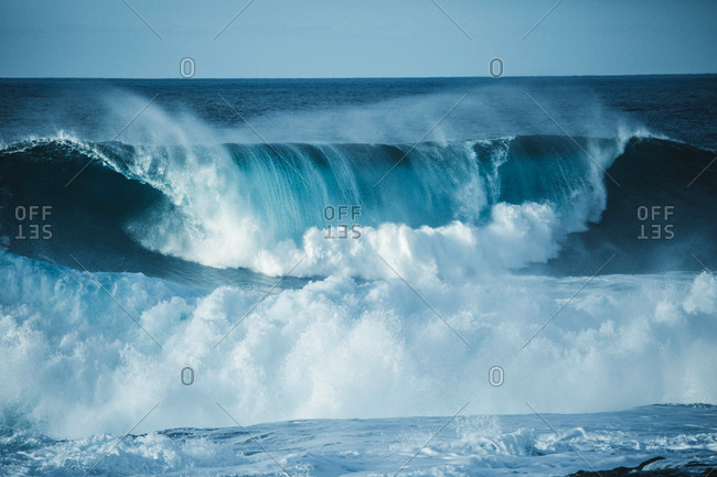 Scenic view of a big wave breaking in the sea against clear sky