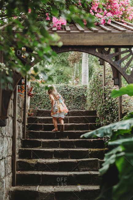 Young girl climbs stone staircase in lush tropical garden on St Kitts