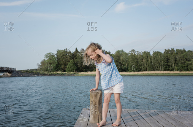 young girl stood on a jetty looking at the water at the beach