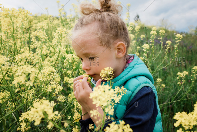 young girl sat in a field of flowers smelling a flower