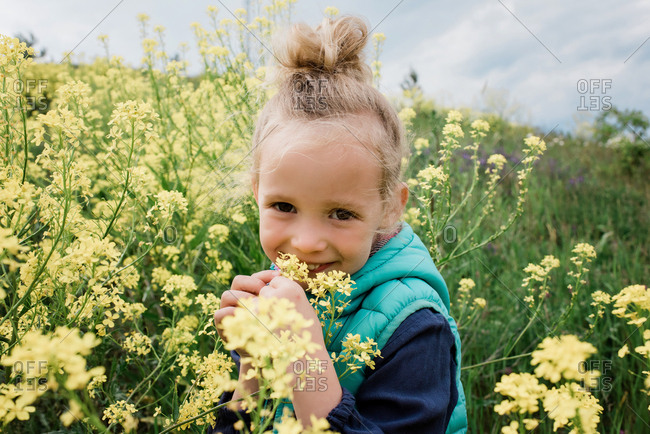 portrait of a young girl sat in a field of yellow flowers smiling