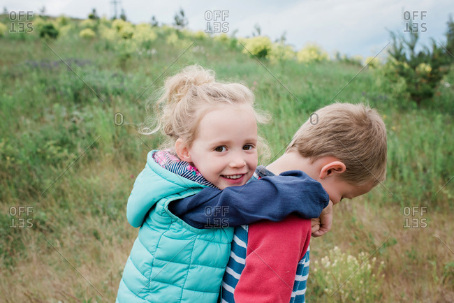 boy giving a girl a piggy back in a field of flowers