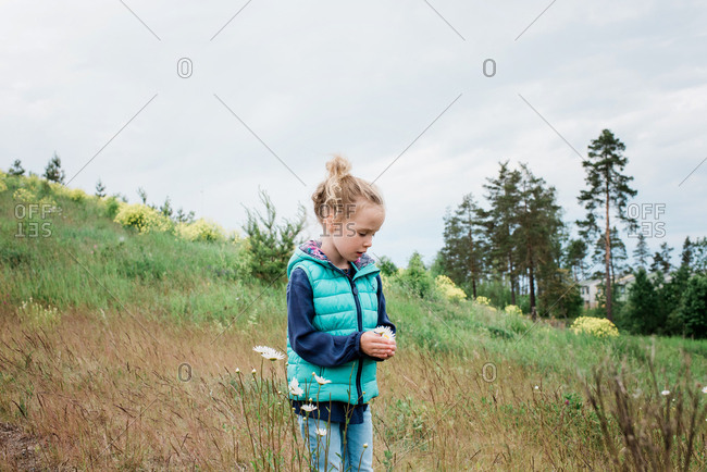 young girl stood in a field holding a bunch of flowers