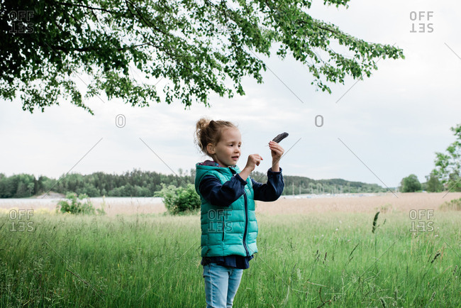 young girl stood in a field holding a feather looking happy