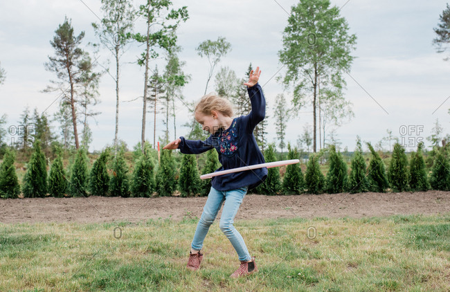 young girl in her garden playing with a hula hoop