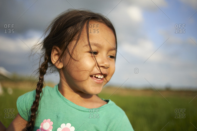 Headshot of a cute young Asian girl happily smiling in summer sunshine