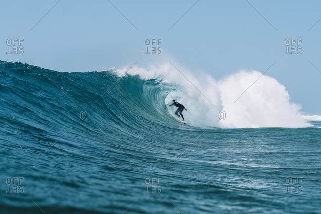 Pulled back view of a surfer in a barrel against a blue sky