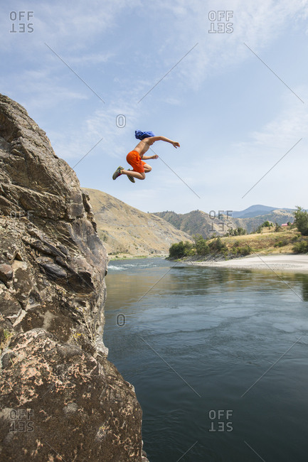 Boy, age 11 jumping off a large cliff into the Salmon River, Idaho.