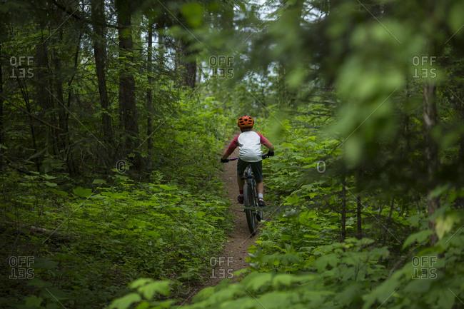 Boy, age 11 riding his mountain bike on a trail through lush forest