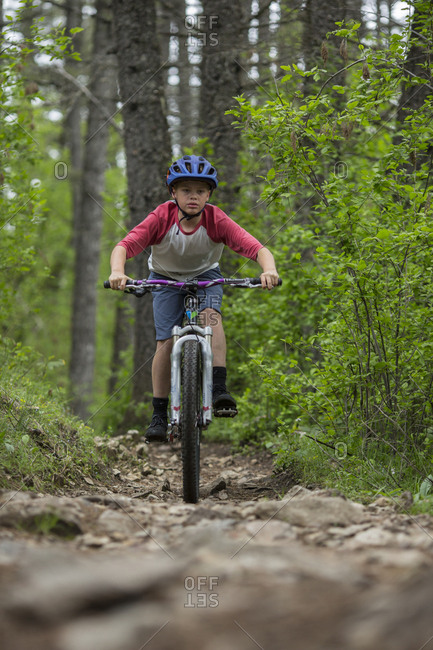 Head on view of boy, age 11 focused on trail while mountain biking.