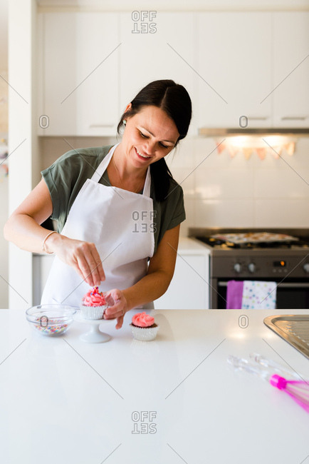 A baker woman smiling as she decorates a pink cupcake