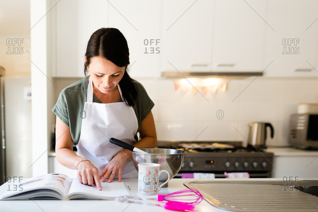A female baker reading a cookbook while baking cupcakes