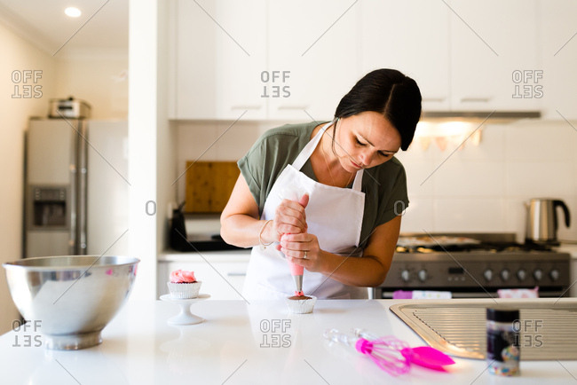 A woman decorating a cupcake with frosting in her kitchen