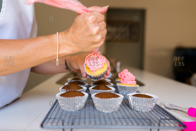 A female's hands decorating cupcakes with pink frosting