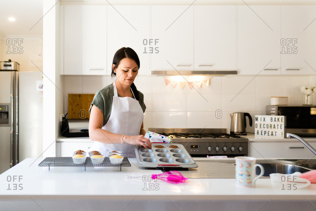 A woman baking cupcakes in her kitchen