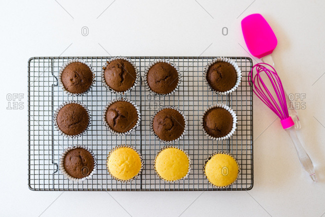 Flat lay of cupcakes cooling on cooling rack with baking tools