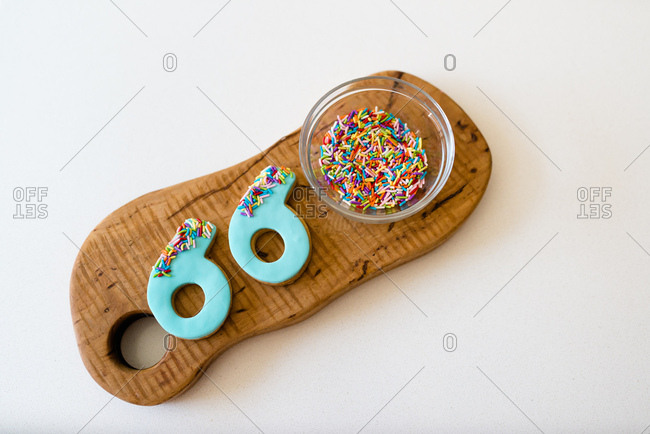 Flat lay of decorated number cookies with sprinkles on a wooden board