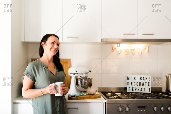 A female baker smiling in her kitchen with baked goods holding a mug