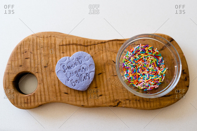 Flat lay of a purple decorated bookie with a bowl of sprinkles