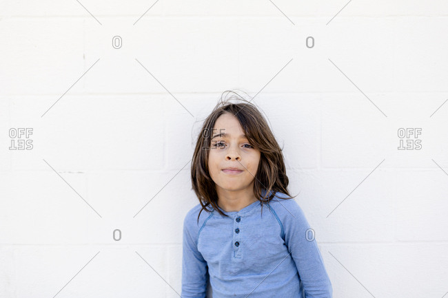 Portrait of cool boy with long hair against white wall