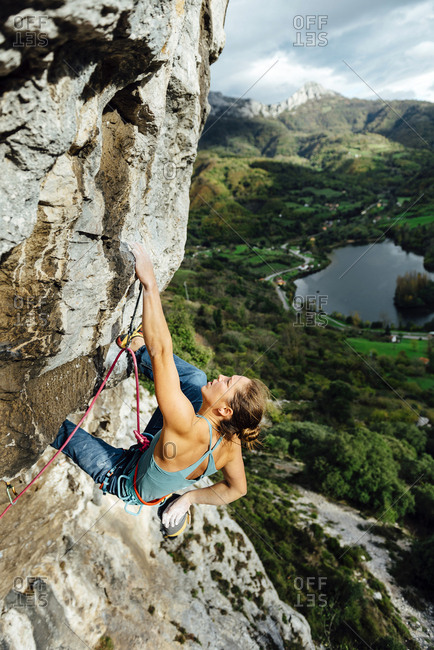 Young woman climbing rock cliff against green fields and mountains