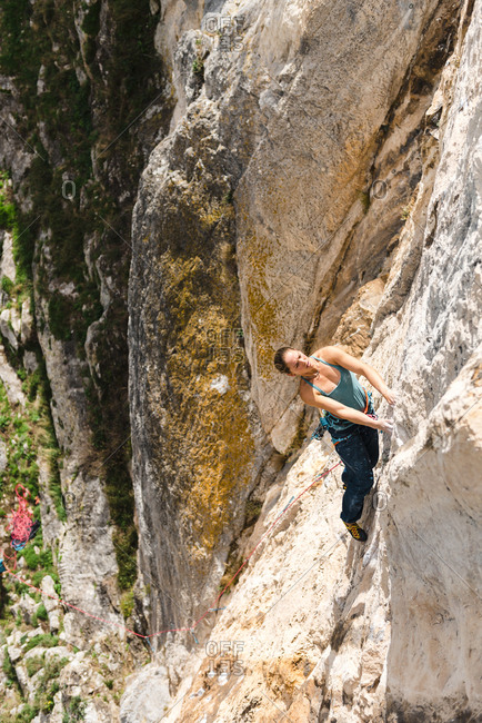 From above view of woman rock climber resting in limestone wall